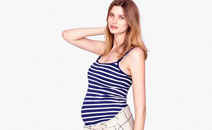 Modelo embarazada tocandose el cuello con el brazo derecho